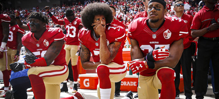 Then-San Francisco 49ers quarterback Colin Kaepernick, center, with Eli Harold and Eric Reid, right, kneel during the national anthem before their NFL game in 2016. (photo: Nhat V. Meyer/Bay Area News Group/Getty Images)