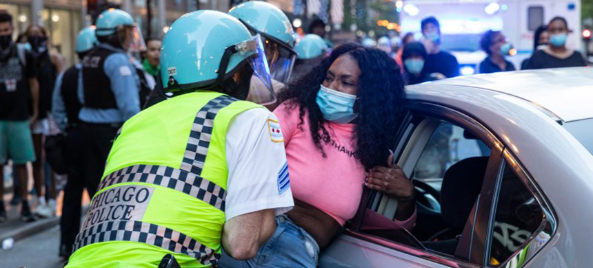 Police officers arrest a woman during protests in Chicago on May 30 following the killing of George Floyd by Minneapolis police. (photo: Natasha Moustache/Getty Images)
