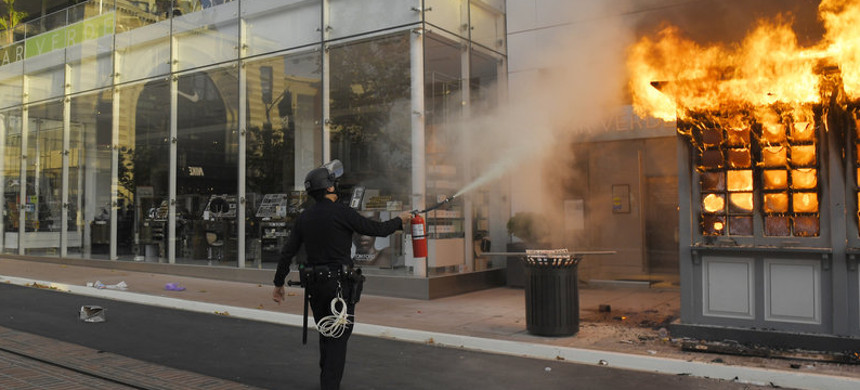 An officer tries to put out a fire at a police kiosk at The Grove shopping center in Los Angeles during a protest last month over the death of George Floyd. (photo: Mark J. Terrill/AP)