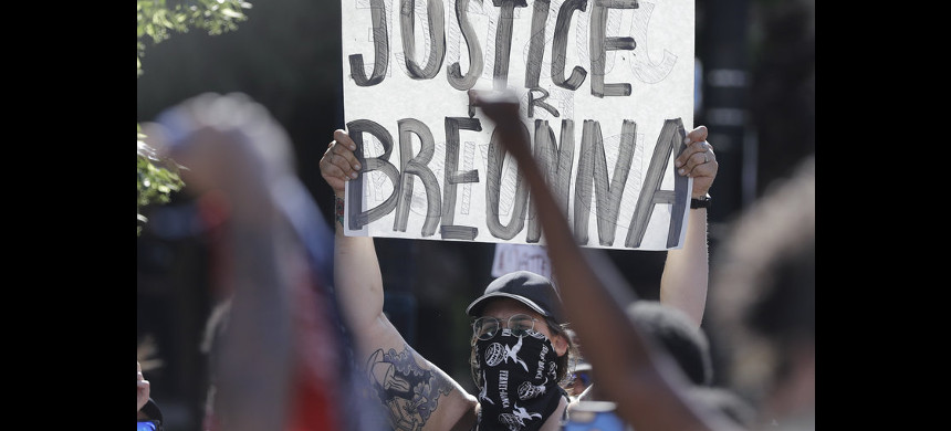 A protester holds a sign during a June 1 protest over the deaths of George Floyd in Minneapolis and Breonna Taylor in Louisville, Ky. (photo: Darron Cummings/AP)