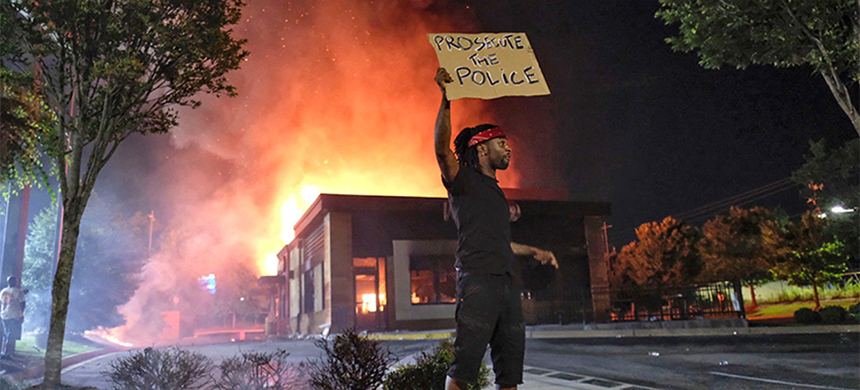 A protester hold a sign as the Atlanta Wendy's where Rayshard Brooks was fatally shot by police. (photo: AP)
