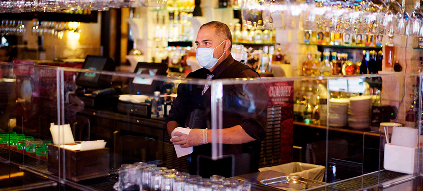 A bartender wears gloves and a mask while taking orders amid the coronavirus pandemic on May 1, 2020, in Houston. (photo: Mark Felix/AFP/Getty Images)