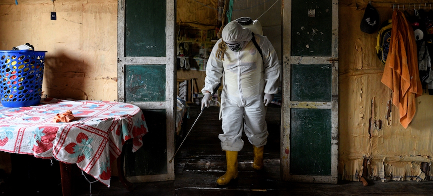 A local volunteer disinfects a home with a chlorine solution, in Zapotal, Ecuador. (photo: Santiago Arcos/Reuters)