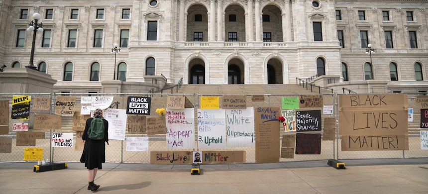 Julia Iwaszek looked Friday at signs posted on a gate surrounding the Minnesota State Capitol during a rally to commemorate Juneteenth in St. Paul. (photo: Renee Jones Schneider/Star Tribune)