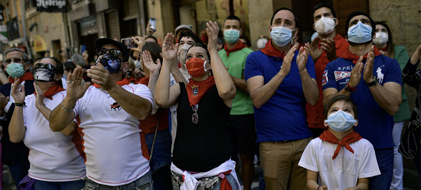 Residents wear faces mask to protect against coronavirus and wear San Fermin's red kerchief as people march the route of the running of the bulls in Pamplona, northern Spain. Spain reopened its borders to European tourists Sunday, June 21, 2020. (photo: Alvaro Barrientos/AP)