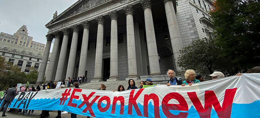 Protesters held signs outside courthouse on the opening day of a trial of Exxon in 2019. (photo: Eduardo Munoz Alvarez/Getty)