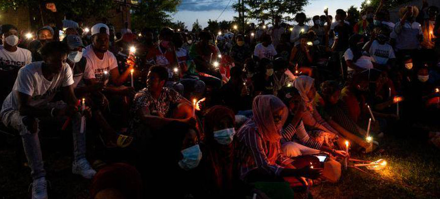 People gather for a candlelight vigil in memory of Hachalu Hundessa at the Oromo Community of Minnesota building in St. Paul on June 30. (photo: AP)