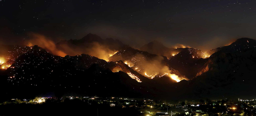 A wildfire burning in the Santa Catalina Mountains looms over homes in Oro Valley, Arizona. (photo: Kelly Presnell/AP)