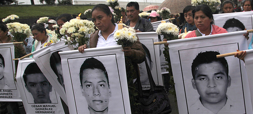 Maria Telumbre, center, holding a poster with the image of her missing son, Christian Alfonso Rodriguez, in Mexico City in 2014. (photo: Marco Ugarte/AP)