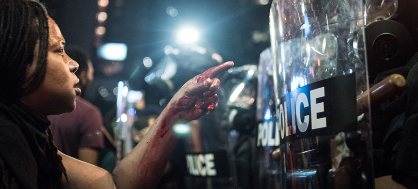 With blood covering her hand and arm, a woman points at a police officer on September 21, 2016 in Charlotte, NC. The governor had declared a state of emergency in the city after clashes during protests in response to the fatal shooting of of 43-year-old Keith Lamont Scott. (photo: Sean Rayford/Getty Images)