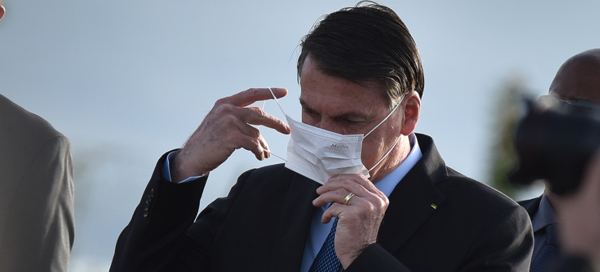Brazil's President Jair Bolsonaro wears a face mask when arrives in front of Alvorada Palace. (photo: Andre Borges/Getty)