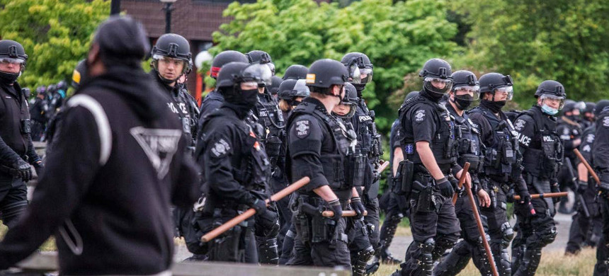 Officers armed with batons clear Seattle's Cal Anderson Park. (photo: AP)