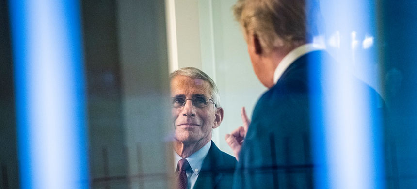 President Trump, seen through a window, speaks with Anthony S. Fauci after a briefing in April. (photo: Jabin Botsford/WP)