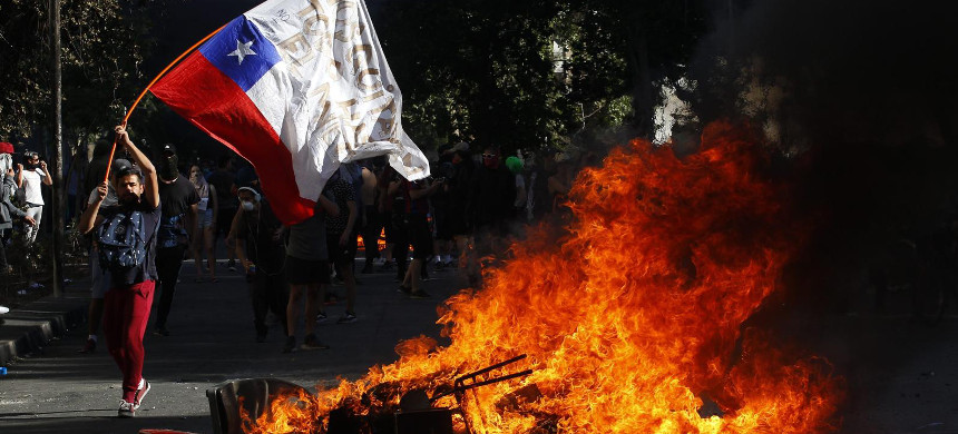 A demonstrator waves a Chilean flag next to a fire in Santiago. (photo: Getty)
