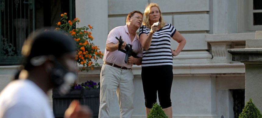 Mark and Patricia McCloskey stood in front of their house in St. Louis on June 28 as protesters marched to the nearby house of St. Louis Mayor Lyda Krewson. (photo: Laurie Skrivan/AP)