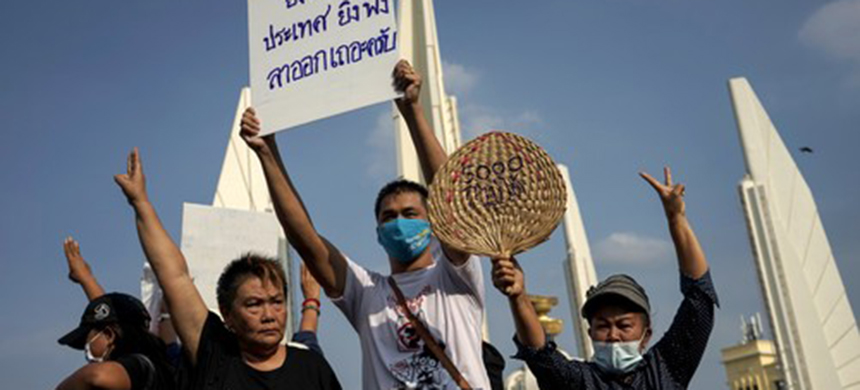 Protesters hold a sign that reads 'The longer you stay, the more devastation to the country, please resign' as they take part in an anti-government demonstration in Bangkok. (photo: Aiden Jones/AFP)