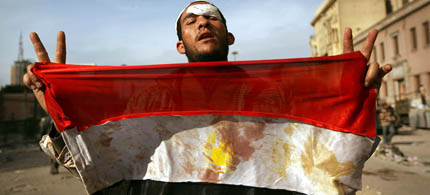 An anti-government protester holds a blooded Egyptian flag in Tahrir Square. (photo: Peter Macdiarmid/Getty Images)