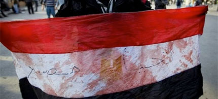A pro-democracy demonstrator stands in Tahrir Square holding an Egyptian flag stained with blood, 02/02/11. (photo: Tara Todras-Whitehill/AP)