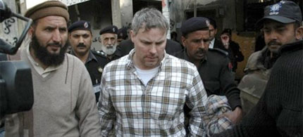 Pakistani security officials escort Raymond Allen Davis, a US CIA contractor, center, to a local court in Lahore, Pakistan, 01/28/11. (photo: Hamza Ahmed/AP)