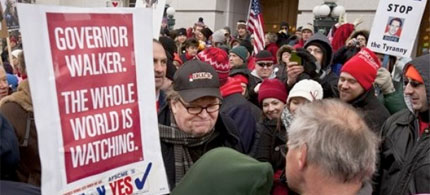 Filmmaker Michael Moore, surrounded by admirers and well-wishers, on the 18th day of labor protests in Madison, Wisconsin. (photo: AP)