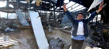 A Libyan man flashes victory signs as he stands amid the rubble of a navy facility that was hit by a coalition airstrike in Tripoli, Libya, 03/22/11. (photo: Mohamed Messara/EPA)