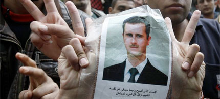 Syrian university students in Lebanon flash victory signs as they carry a picture of Syria's President Bashar al-Assad. (photo: Reuters)v