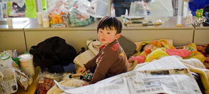 A Japanese child evacuee rests at a temporary shelter in Kesennuma, 03/17/11. (photo: Shiho Fukada/IHT)