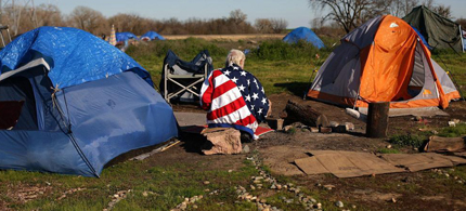 A homeless resident of a tent city in Sacramento, California wears an American flag jacket, as more people join the ranks of the unemployed and as homes slip into foreclosure, 03/10/09. (photo: Justin Sullivan/ Getty Images)