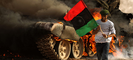 A Libyan rebel holds the Kingdom of Libya flag as he walks past a burning tank at a site bombed by the coalition air force in the town of Ajdabiya, 03/26/11. (photo: Patrick Baz/AFP/Getty)