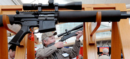 A man checks out a rifle at the 140th National Rifle Association exhibit in Pittsburgh. (photo: AP)