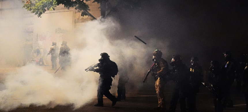 Federal officers walk through tear gas while dispersing a crowd during a July 21 protest in Portland, Oregon. A temporary restraining order on Thursday blocked federal agents from knowingly targeting journalists and legal observers. (photo: Nathan Howard/Getty)