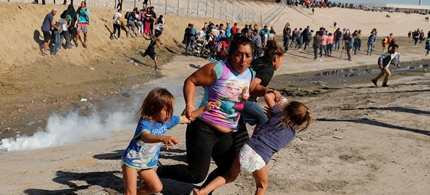 A family runs away from tear gas in front of the border wall between the U.S. and Mexico in Tijuana. (photo: Kim Kyung-Hoon/Reuters)