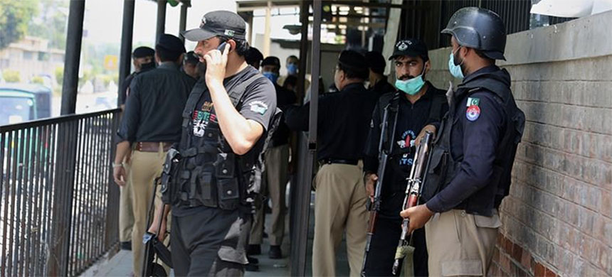 Police officers gather at an entry gate of Peshawar's district court following the killing of Tahir Ahmad Naseem. (photo: Muhammad Sajjad/AP)