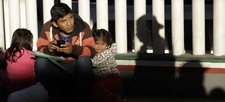 An immigrant looks on with his children as they wait to hear if their number is called to apply for asylum in the United States at the border in Tijuana, Mexico, Jan. 25, 2019. (photo: Gregory Bull/AP)