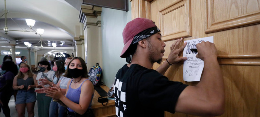 Matthew Bruce of Des Moines, Iowa, signs a note during a Black Lives Matter demonstration outside Iowa Gov. Kim Reynolds' office in June. The Republican governor has signed an executive order restoring voting rights to people convicted of a felony. (photo: Charlie Nelbergall/AP)