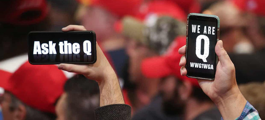 Trump supporters hold up their phones with QAnon messages at a campaign rally at the Las Vegas convention center on 21 February 2020. (photo: Mario Tama/Getty Images)