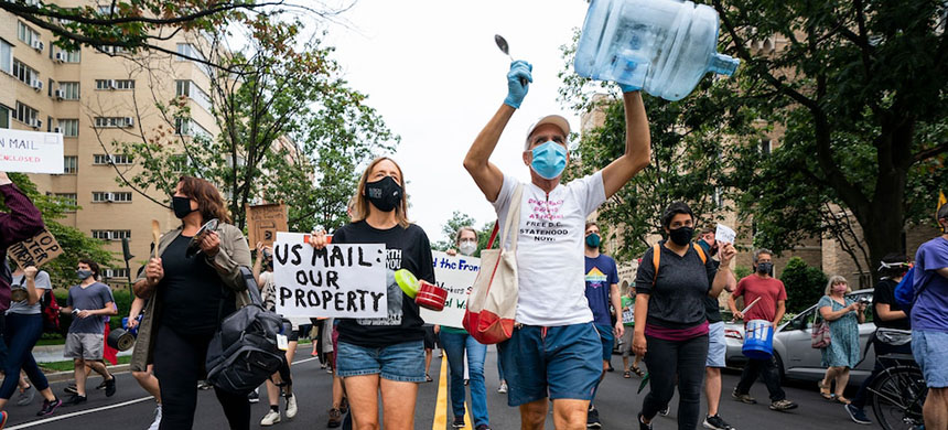 Supporters of the activist group Shut Down DC march to the apartment of Postmaster General Louis DeJoy in Washington on Saturday. (photo: Jim Lo Scalzo/EPA-EFE/REX/Shutterstock)