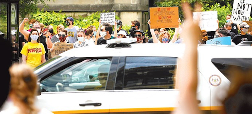 A police vehicle passes protesters in Pittsburgh. (photo: Jared Wickerham/Pittsburgh City Paper)