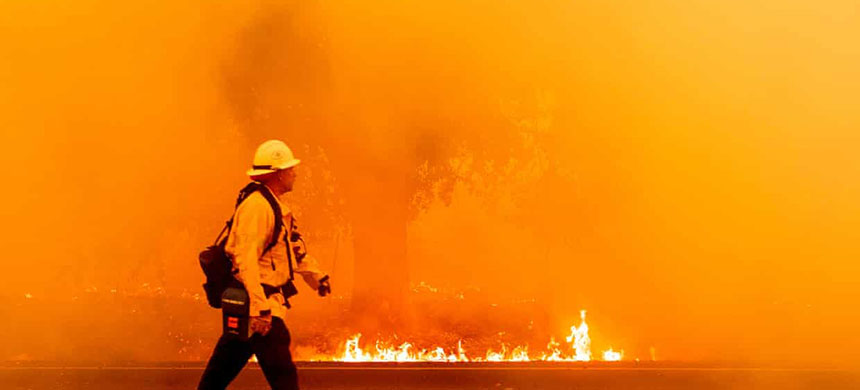 A Pacific Gas and Electric firefighter walks down a road as flames approach in Fairfield, California, on 19 August. (photo: Josh Edelson/AFP/Getty Images)