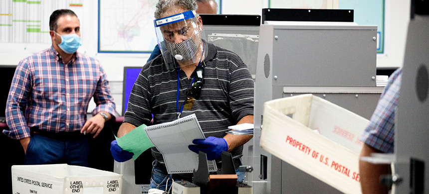 Election workers in Miami-Dade County in Florida processed mail-in ballots for the state's primary election last month. Polling suggests that significantly more Democrats plan to vote by mail in November. (photo: Scott McIntyre/NYT)