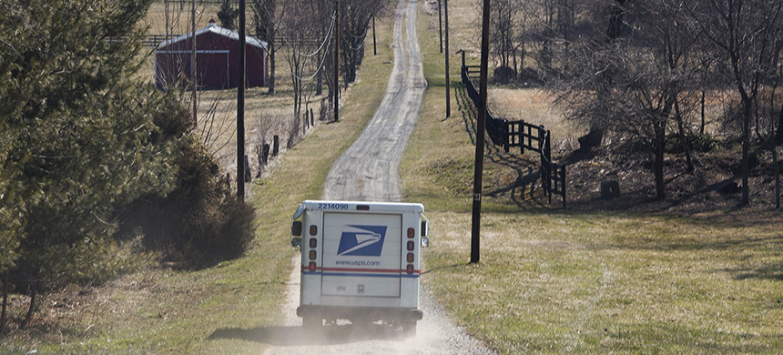 A U.S. Postal Service truck delivers mail in Charles Town, W.V. (photo: Jared Soares/Redux)