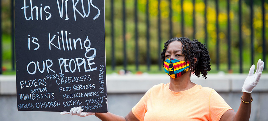 Alice Gaskins holds sign that says 'This Virus is Killing Our People' in front of the Massachusetts State House as people perform a 'funeral procession' for essential workers that have been sick with or died from Covid-19 on May 25, 2020. (photo: Blake Nissen/The Boston Globe/Getty Images)