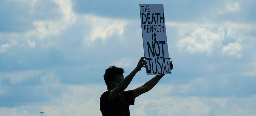 A death penalty protestor carries a sign across the street from the federal prison complex in Terre Haute, Ind., on Aug. 26, 2020. (photo: Michael Conroy/AP)