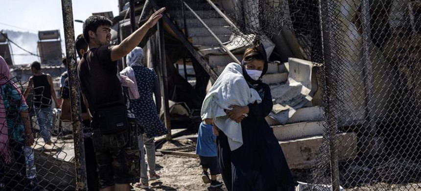 A refugee woman holding a baby passes the burned debris after a fire in the Moria refugee camp on the northeastern Aegean island of Lesbos, Greece, on Wednesday. (photo: Petros Giannakouris/AP)