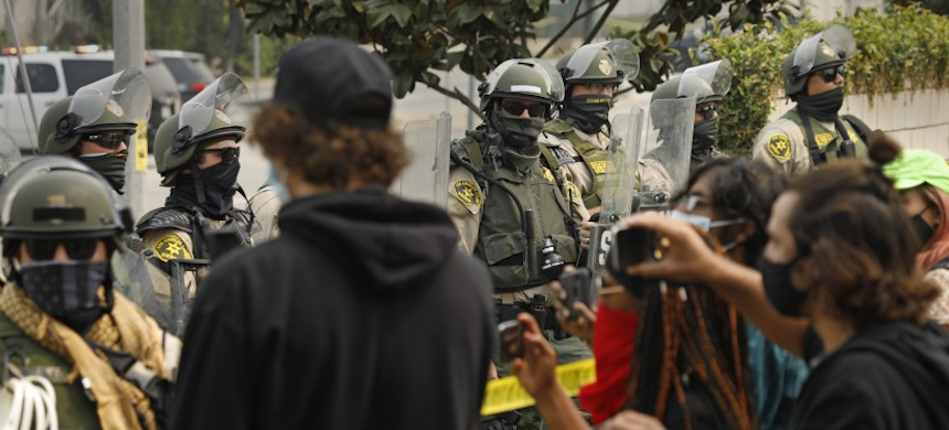 L.A. County sheriff's deputies in riot gear watch as activists hold a news conference on Friday in South L.A. (photo: Carolyn Cole/LA Times)