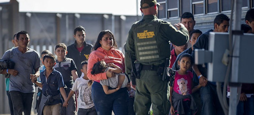 Migrants are loaded onto a bus by Border Patrol agents in El Paso, Texas. (photo: Joe Raedle/Getty Images)