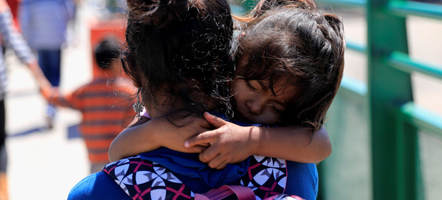 Central American migrant carries her child just after she was sent to Mexico from the U.S. (photo: Carlos Jasso/Reuters)