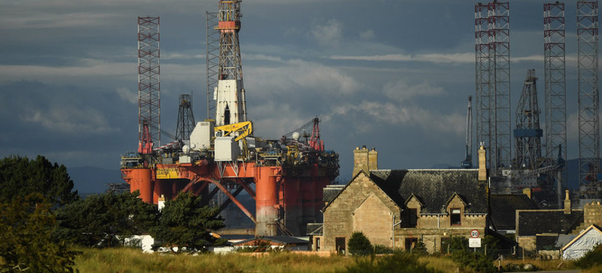An oil rig towers over houses last week in Nigg, Scotland. Major players in the oil industry expect depressed oil demand and low prices to continue well into next year. (photo: Peter Summers/Getty)
