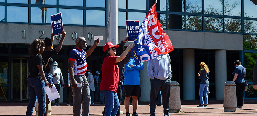Supporters of President Trump gathered outside the Fairfax County Government Center with flags and banners, chanting near residents who were waiting in line for early voting. (photo: Kenny Holston/NYT)
