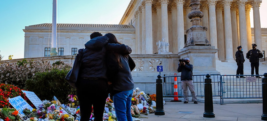 The flag flies at half-mast and visitors examine remembrances left in front of the Supreme Court on the morning after the announcement of the death of Justice Ruth Bader Ginsburg. (photo: Bill O'Leary/TWP)